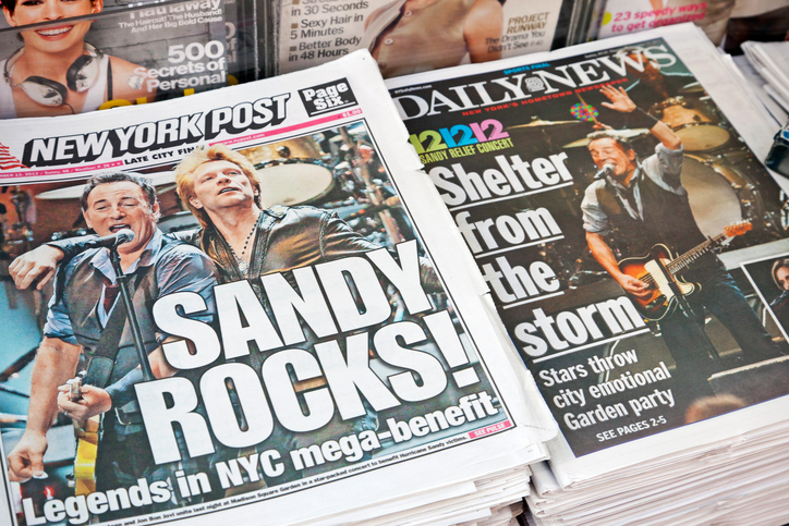 """New York City, USA - December 13, 2012: New York Post and Daily News in a newsstand on the street with headlines on the front pages reporting the 121212 Concert for Hurricane Sandy Victims in the sold-out Madison Square Garden. Bruce Springsteen and Jon Bon Jovi can be seen."""